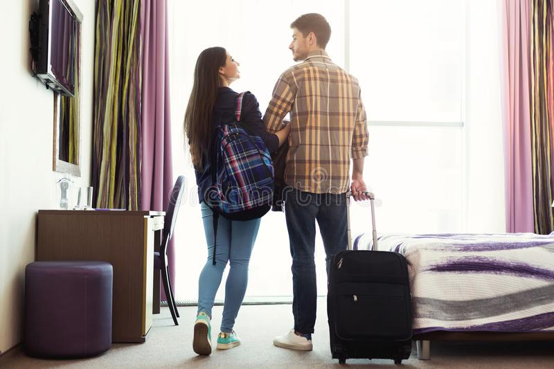 Young couple with luggage in hotel room. Young happy couple with luggage in hotel room. Just married men and women arrived to resort, romantic vacation and royalty free stock photos