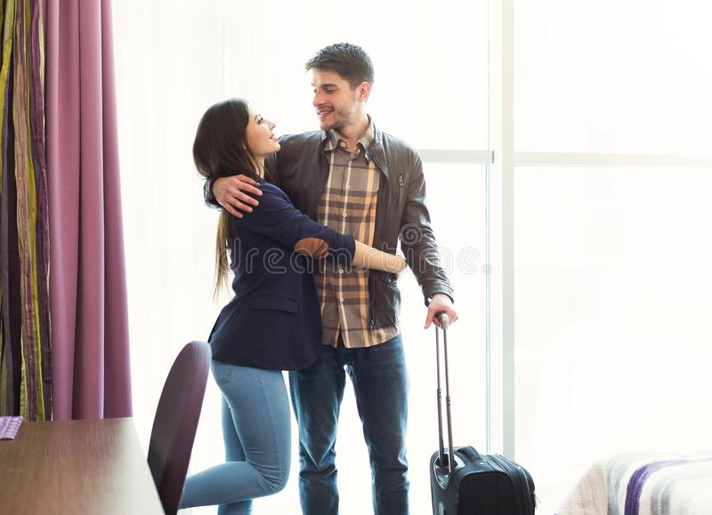 Young couple with luggage in hotel room. Young happy couple with luggage in hotel room. Just married men and women arrived to resort, romantic vacation and stock photography