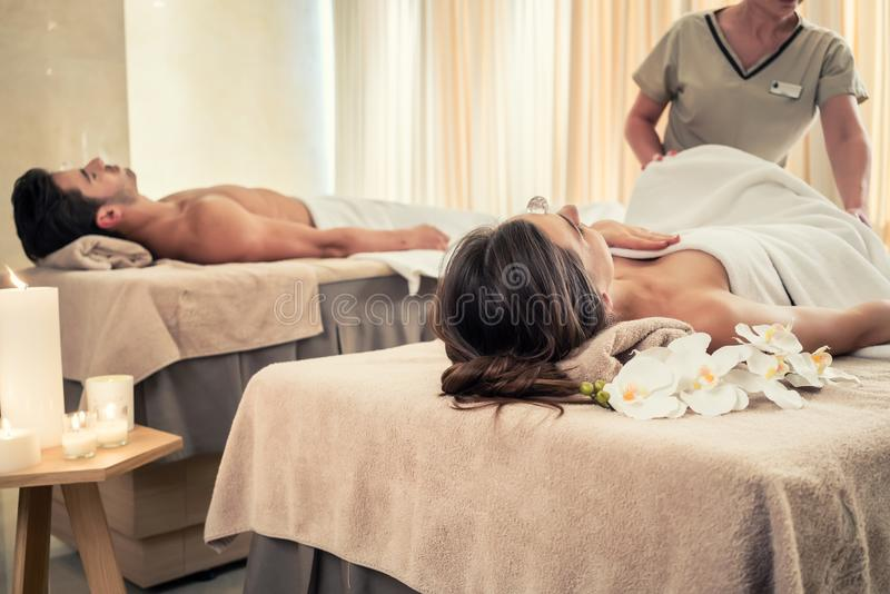 Young couple lying down on massage beds during crystal therapy stock photography