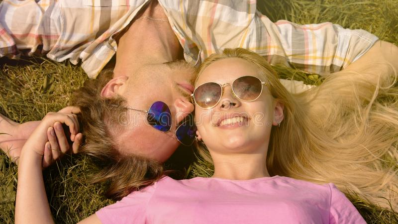 Young couple lying on grass, holding hands, boyfriend kissing girlfriend, date stock photo