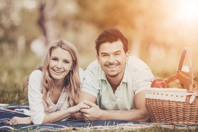 Young Couple Lying on Green Grass in Summer Park. royalty free stock photography