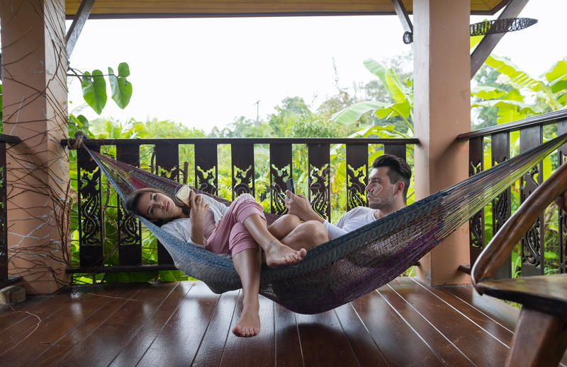 Young Couple Lying In Hammock On Terrace Tropical Hotel, Man And Woman Using Cell Smart Phone Chatting Tropic Holiday. Vacation Green Forest stock image