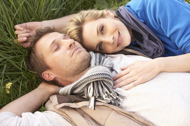 Young couple lying together on grass royalty free stock photography
