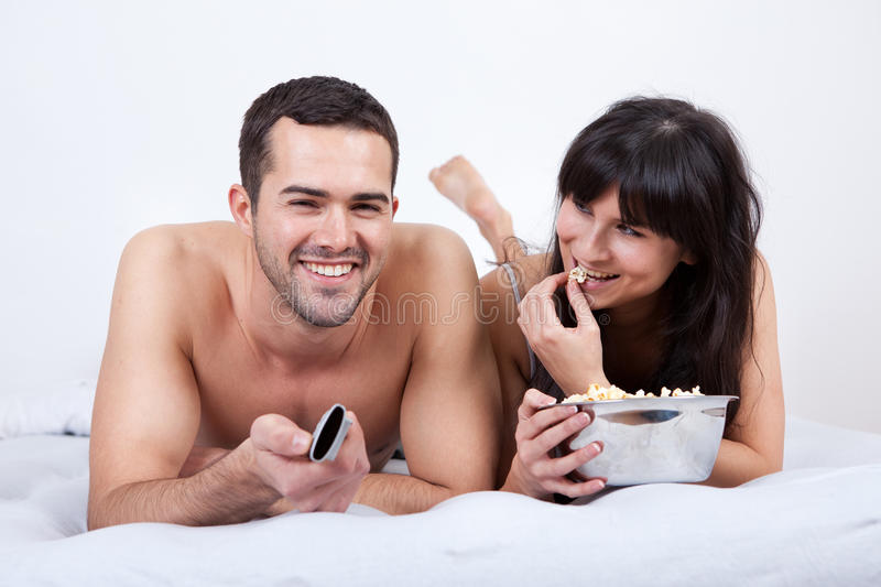 Young Couple Lying Up In Bed And Watching TV Royalty Free Stock Photos