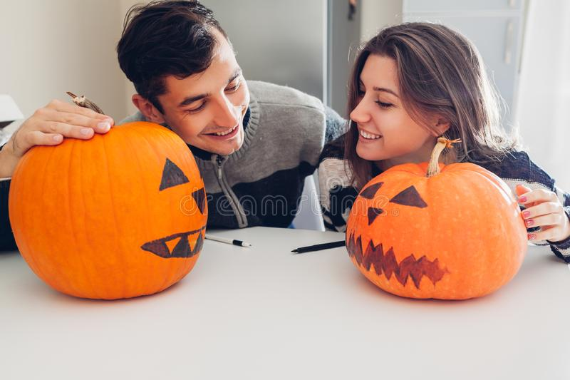 Young couple making jack-o-lantern for halloween on kitchen. Man and woman comparing their pumpkins stock photo