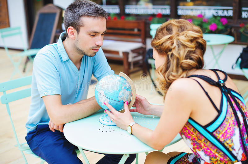 Young couple making plans for their next travel destination. Young couple in cafe making plans for their next travel destination with the globe map royalty free stock image