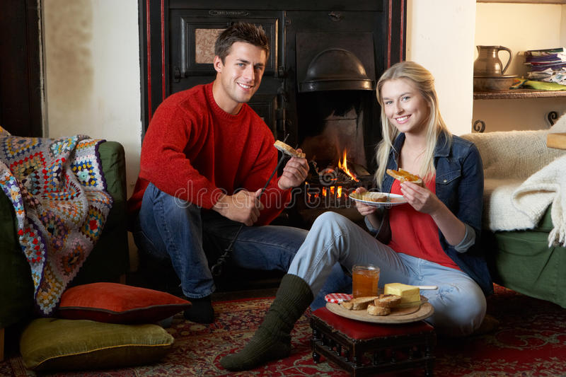Young couple making toast on open fire. Smiling at camera royalty free stock image