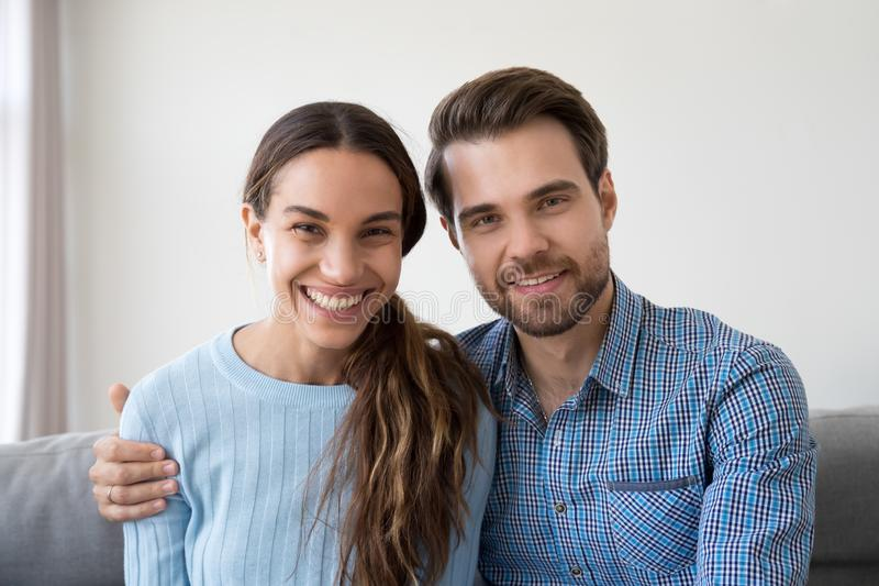 Young couple making video call communicating online or recording. Headshot portrait of happy smiling millennial couple sitting on sofa at home embracing looking royalty free stock images