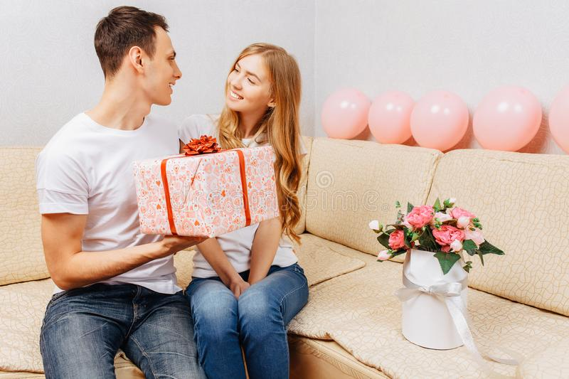 Young couple, man and woman give each other gifts while sitting at home on the couch, valentines day concept. Young couple, men and women give each other gifts stock images
