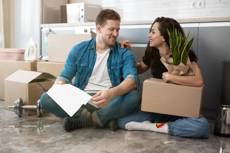 Young couple man and woman looking happy sitting on the floor in their new appartment unpacking paper boxes, moving royalty free stock photo