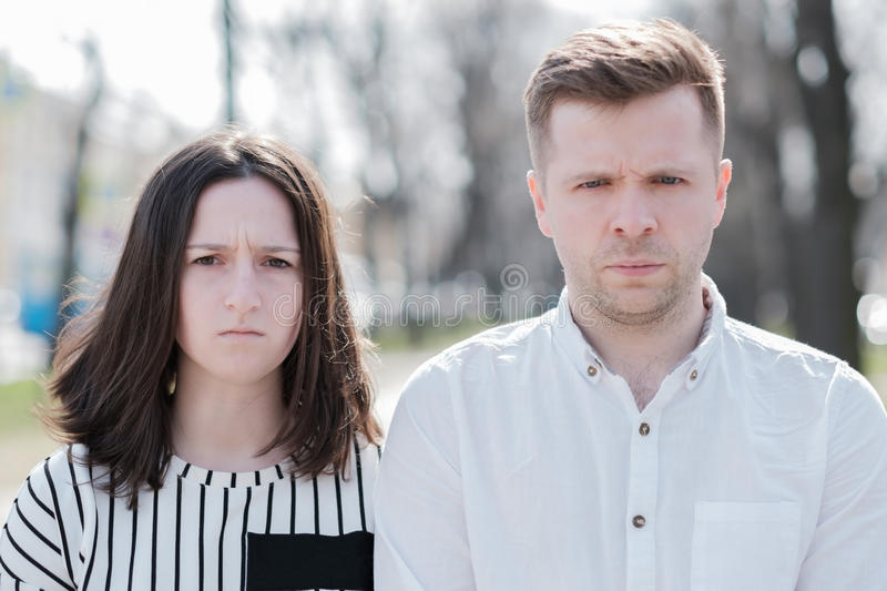 Young couple man and woman looking irritated in camera royalty free stock image