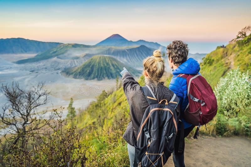 Young couple man and woman meet the sunrise at the Bromo Tengger Semeru National Park on the Java Island, Indonesia. Young couple men and women meet the sunrise royalty free stock photography