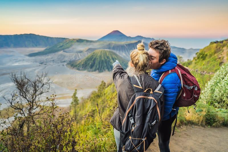 Young couple man and woman meet the sunrise at the Bromo Tengger Semeru National Park on the Java Island, Indonesia. Young couple men and women meet the sunrise stock photo
