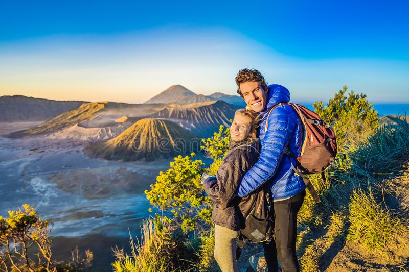 Young couple man and woman meet the sunrise at the Bromo Tengger Semeru National Park on the Java Island, Indonesia. Young couple men and women meet the sunrise royalty free stock photos