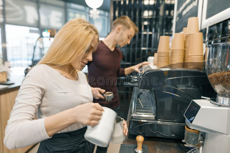 Young couple man and woman owners small business coffee shop, working near coffee machines, making drinks. Young couple men and women owners small business royalty free stock photography