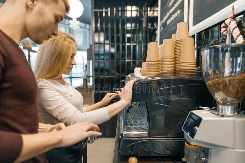 Young couple man and woman owners small business coffee shop, working near coffee machines, making drinks. Young couple men and women owners small business royalty free stock image