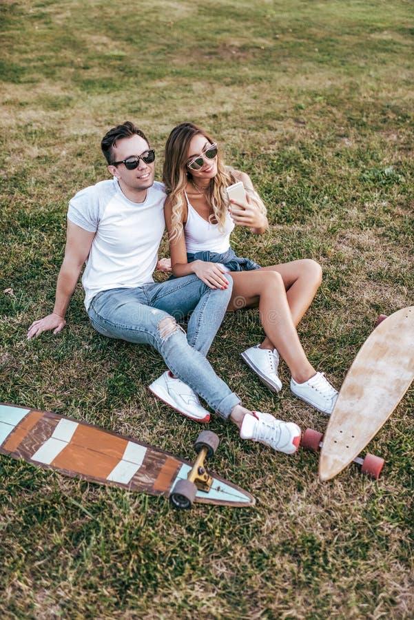 Young couple man woman sit grass summer city weekend, happy ones smiling joking having fun. Skateboard board longboard royalty free stock photo