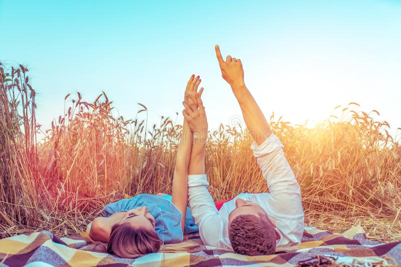 A young couple, man woman, in wheat field summer, lie on rug. Hand gestures indicate stars. Concept love, date, emotion royalty free stock images