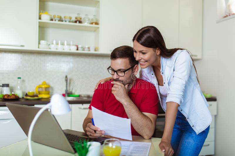 Couple managing finances, reviewing their bank accounts using laptop computer at modern kitchen stock image