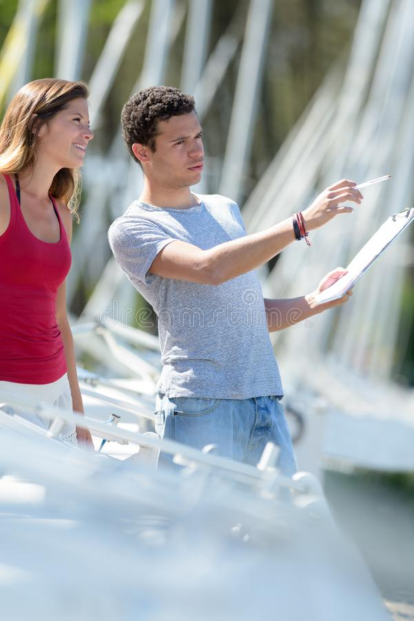 Young couple in marina with clipboard. Marina royalty free stock photos