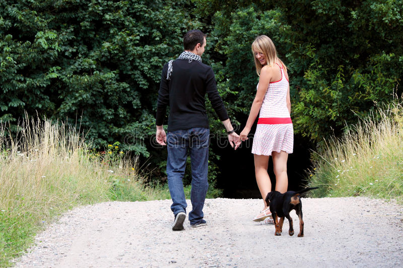 Young couple in meadow. Walking with dog royalty free stock photo