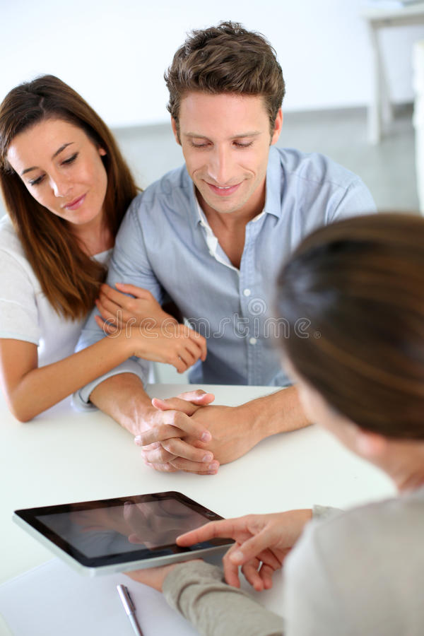 Young couple meeting financial adviser. Businesswoman presenting credit plan to couple stock photos