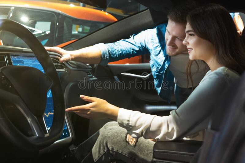 Young couple man and woman checking modern gps navigation system in new vehicle during electric car dealership center visit. Young couple men and women checking royalty free stock image