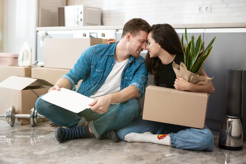 Young couple man and woman looking happy sitting on the floor in their new appartment, hugging, unpacking paper boxes royalty free stock photo