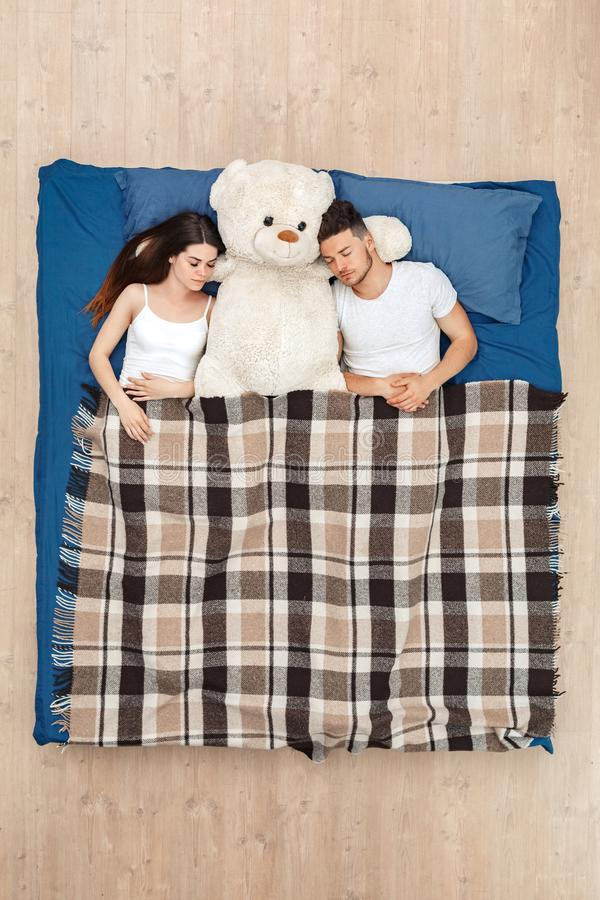 Bedtime. Young couple sleeping on bed top view under blanket with teddy cute royalty free stock photo