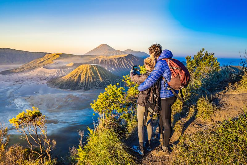 Young couple man and woman meet the sunrise at the Bromo Tengger Semeru National Park on the Java Island, Indonesia. Young couple men and women meet the sunrise royalty free stock photo