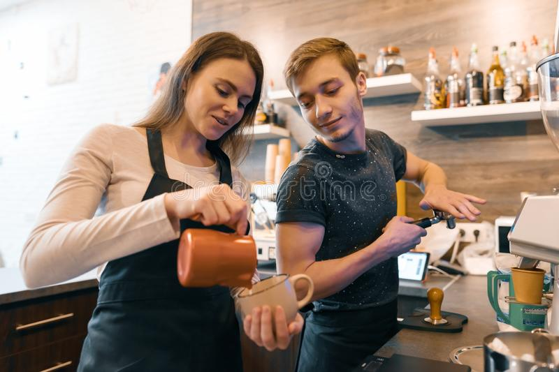 Young couple man and woman owners small business coffee shop, working near coffee machines, making drinks royalty free stock images