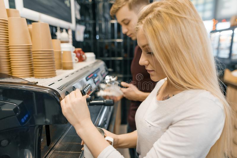 Young couple man and woman owners small business coffee shop, working near coffee machines, making drinks. Young couple men and women owners small business stock images