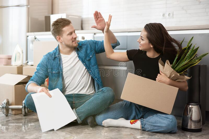 Young couple man and woman sitting on the floor in their new appartment unpacking paper boxes, giving each other high stock images