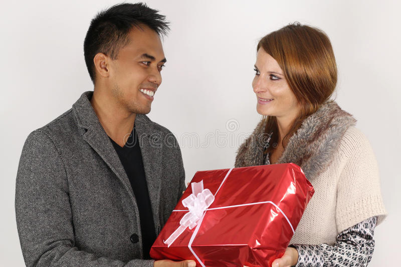 Young couple mixed holding a Christmas present. Couple mixed holding a Christmas present over a white background stock images