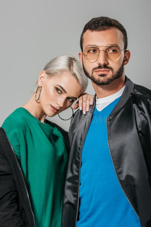 Young couple of modes in stylish outfits looking away. Isolated on grey background royalty free stock image