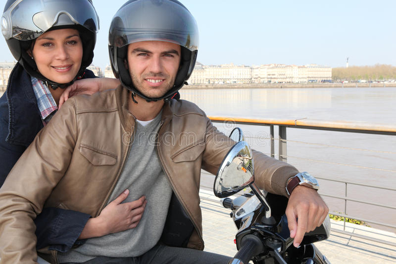 Young couple on a moped royalty free stock image