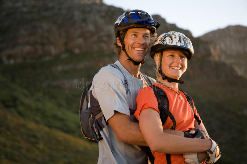 Young couple mountain biking in wilderness, man embracing woman, low angle view royalty free stock photo