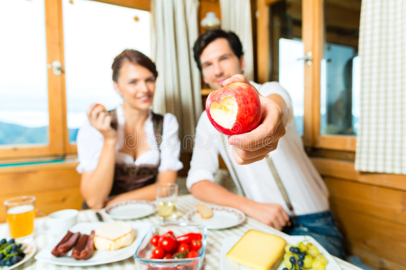 Young couple in mountain chalet eating royalty free stock photos