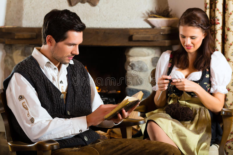 Young couple in mountain hut at fire place stock photography