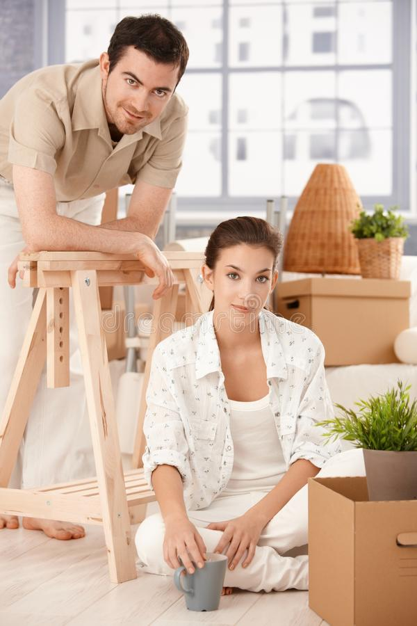 Young couple moving home boxes around smiling. Young couple moving home, sitting on floor, boxes around, smiling, drinking tea stock photography