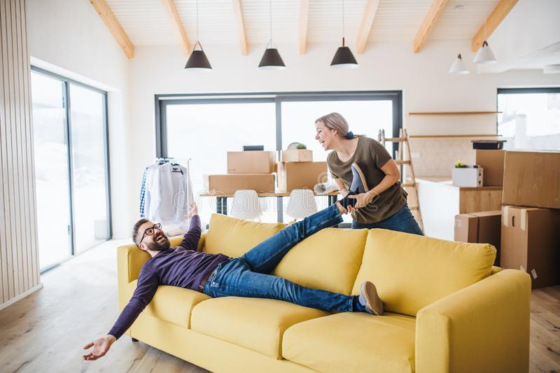 A young couple moving in new home, having fun. royalty free stock image