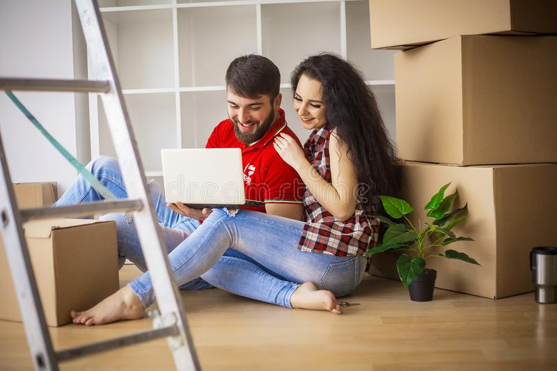 Young couple moving in new home.Sitting and relaxing after unpacking.Looking something on laptop. Young couple stock photo