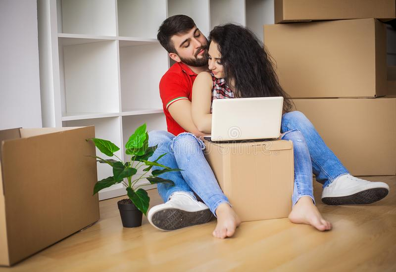 Young couple moving in new home.Sitting and relaxing after unpacking.Looking something on laptop. Young couple royalty free stock photography