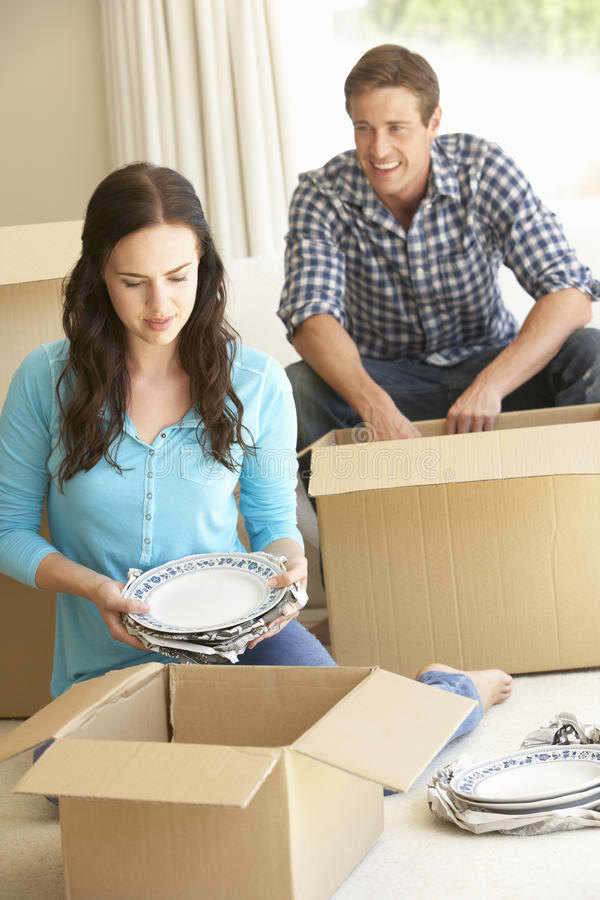 Young Couple Moving Into New Home Unpacking Boxes royalty free stock image
