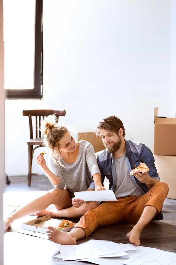 Young couple moving in new house, eating pizza. royalty free stock images