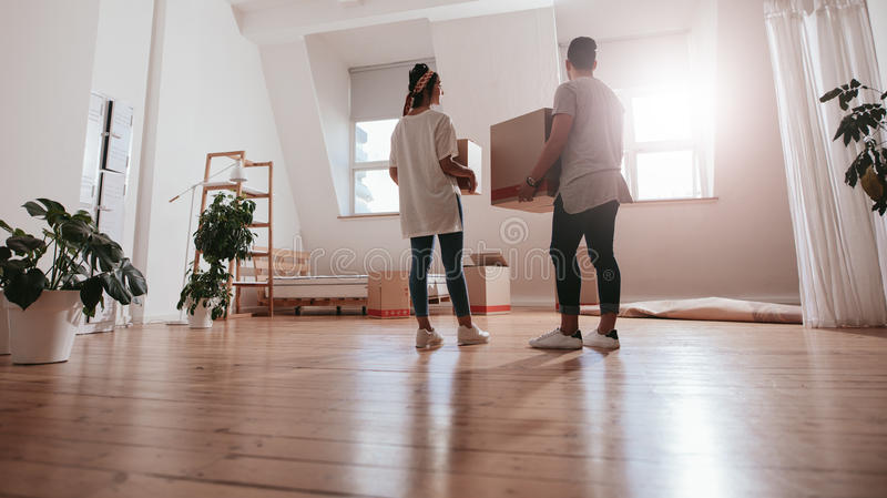 Young couple moving in new house. Full length rear view shot of young couple carrying cardboard box at new home. Young men and women holding boxes and moving in stock image