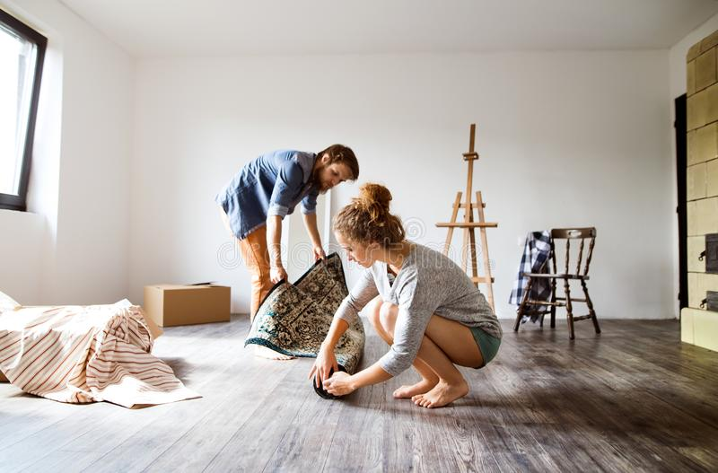 Young couple moving in new house, rolling out carpet. stock photo