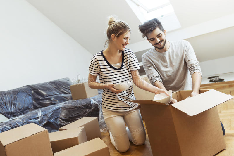Young couple moving into their new home. Boxes stock photos