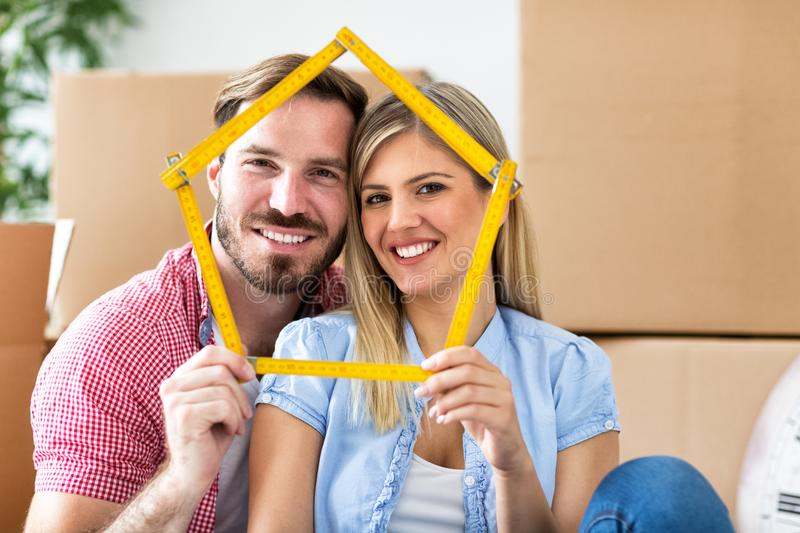 Young couple moving to new home, holding house together and smiling royalty free stock photography