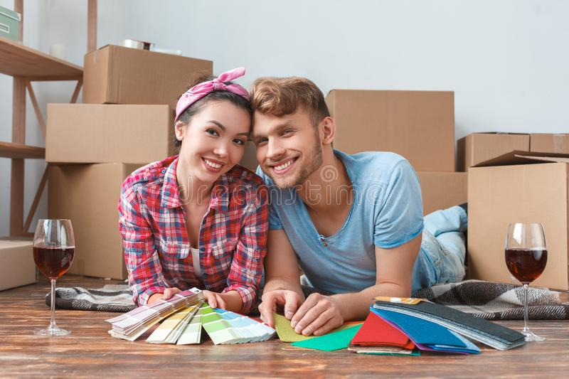 Young couple moving to new place lying holding color palettes drinking wine looking camera happy stock photos